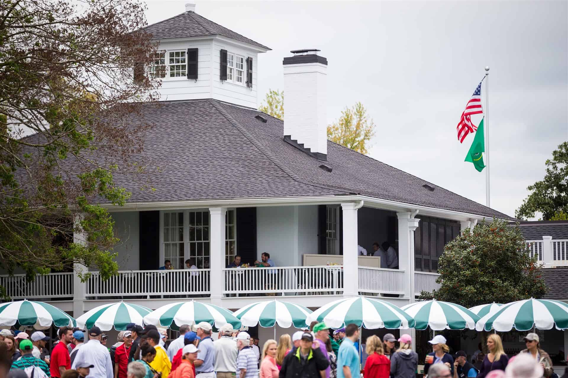 Photograph of the Augusta National clubhouse with the American flag and The Masters flag flying and hundreds of people milling about in excitement.