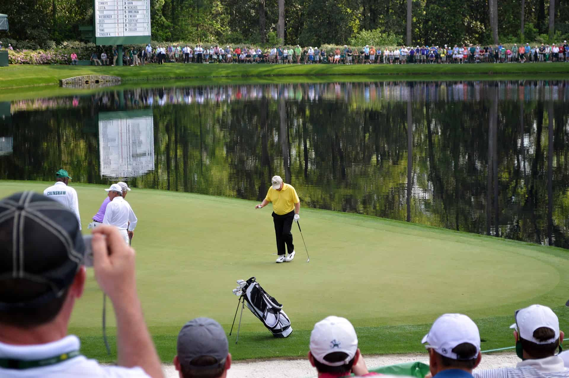 Jack Nicklaus on the green during the par 3 contest with shimmering water in the background, a large crowd in the distance and taken from the perspective of a fan near and overlooking the green.