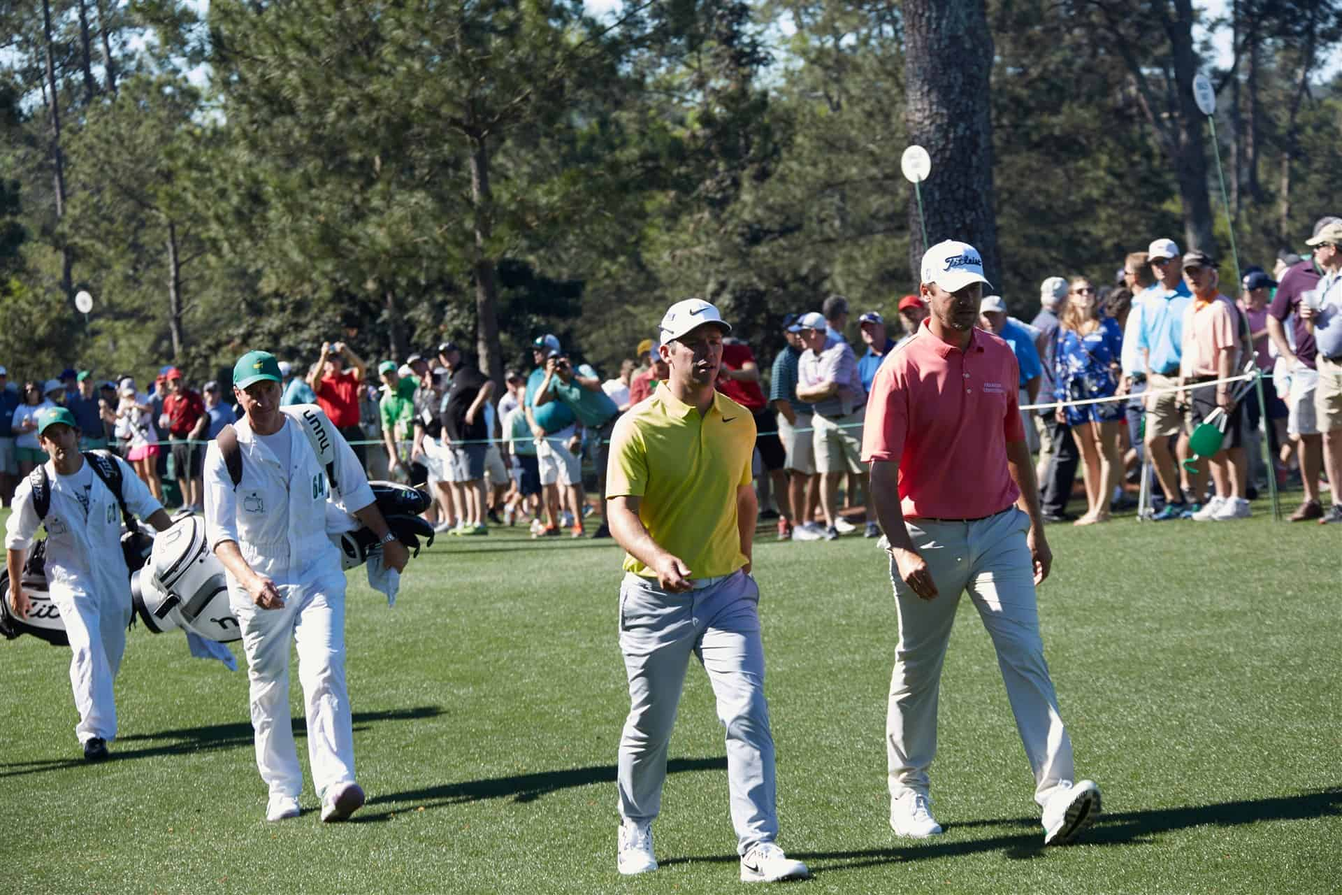 Two golf pros at The Masters practice round walk together along the fairway with their caddies trailing and spectators in the background at Augusta National.